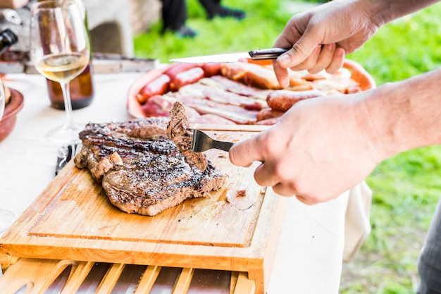 屋外でテーブルに新鮮な焼き肉を切る手のクローズアップ