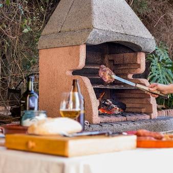 Крупный план руки, приготовленные на гриле мясо с щипцами в открытом барбекю