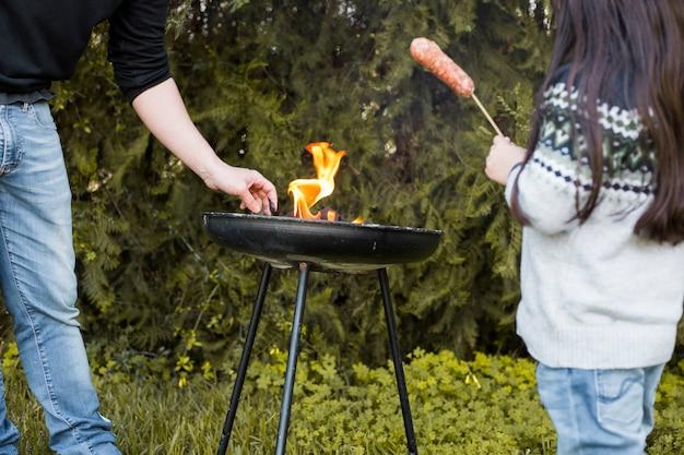 Девушка с колбасой, стоящей рядом с ее отцом, на гриле на переносном барбекю