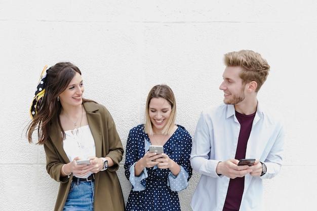 Группа друзей, стоящих возле стены, с помощью мобильного телефона