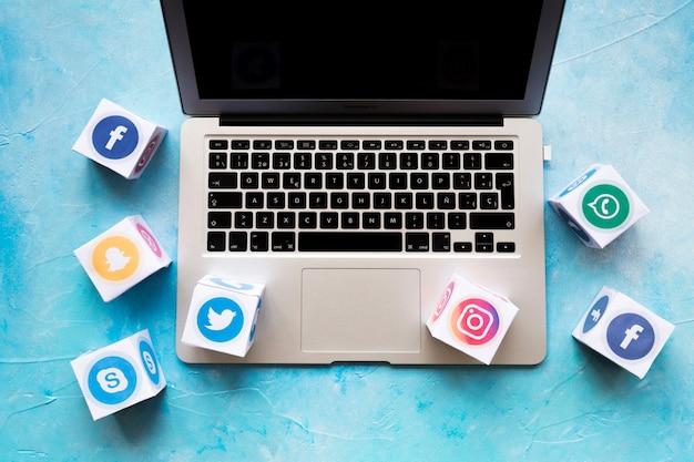 青い背景の上にノートパソコンのソーシャルメディアのアイコンブロック