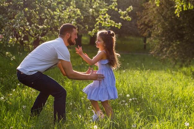 Отец поднимает дочь в парке