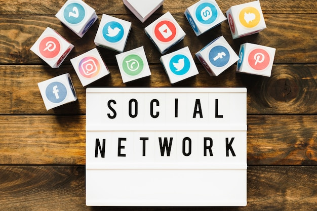 木製テーブル上のソーシャルネットワークのテキストの近くによく知られているネットワークアイコン