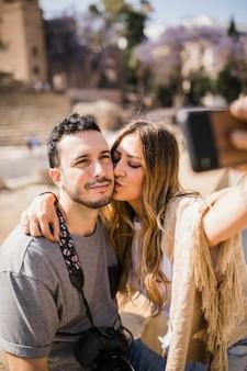 スマートフォンでセルフをする彼女のボーイフレンドにキスする女性