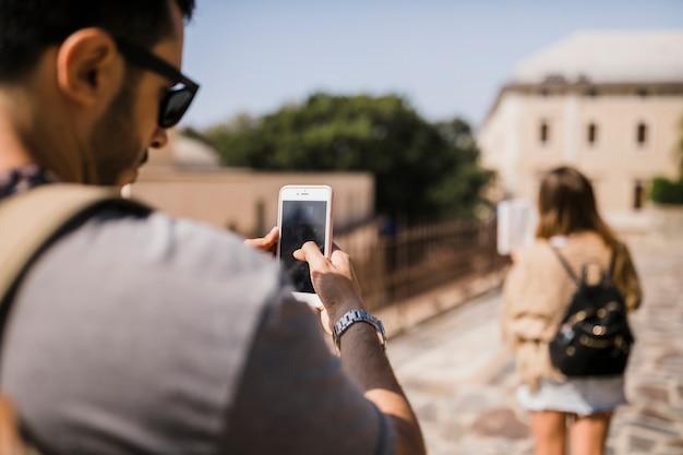 街頭の地図を見ている女性の写真を撮っている男のリアビュー