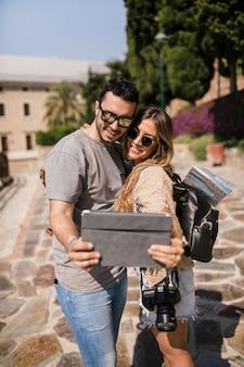 観光客の若いカップルがデジタルタブレットでセルフタイツを撮っています