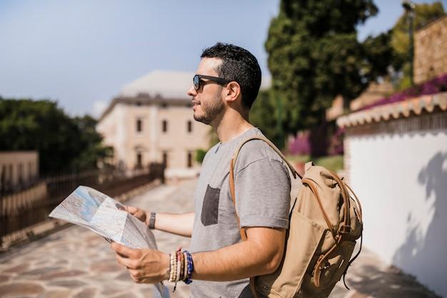 彼の手で地図を保持している男性観光客のクローズアップ