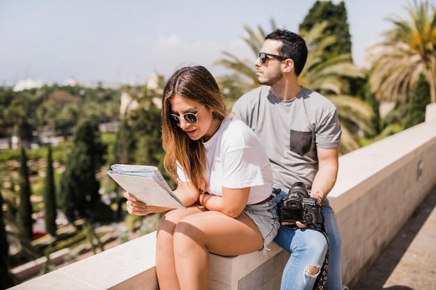 彼女のボーイフレンドと公園に座っている地図で探している女性