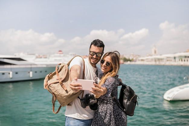 海の前で携帯電話でセルフを撮っているカップルの観光客