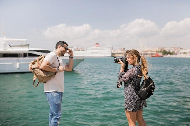海の近くのカメラで彼女のボーイフレンドの写真を撮っている女性