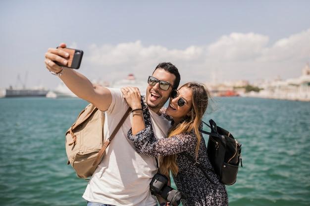 海の近くの携帯電話でセルフポートレートを撮って観光の若いカップルを笑顔