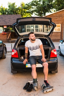 Мужской валторщик сидит на багажнике автомобиля