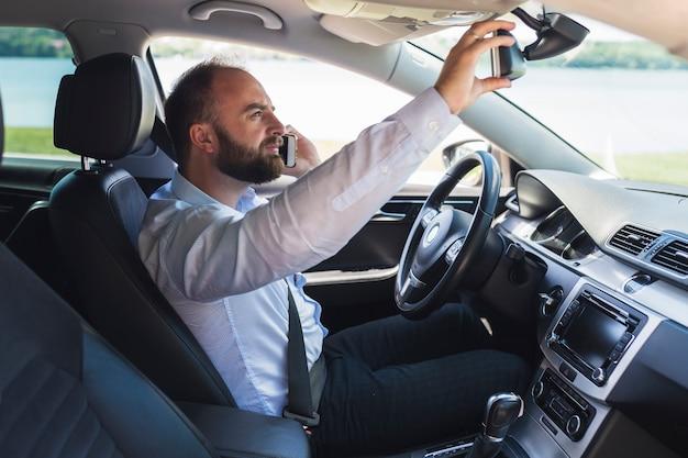 Человек разговаривает по мобильному телефону, настраивая зеркало заднего вида автомобиля
