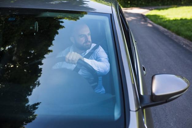 Человек, сидящий внутри автомобиля, видимый через ветровое стекло