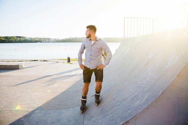 Молодой человек катается на роликах в скейт-парке в солнечный день
