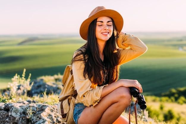双眼鏡を持って岩に座っている笑顔の美しい女性