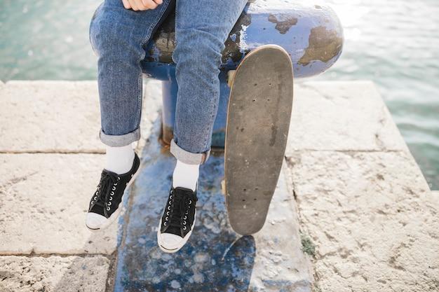 ボラードに座っているスケートボードを持つ男の低断面図