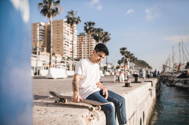 城壁に座っているスケートボードを持つ若い男