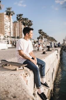 城壁に座っているスケートボードを持つ若い男性スケートボード