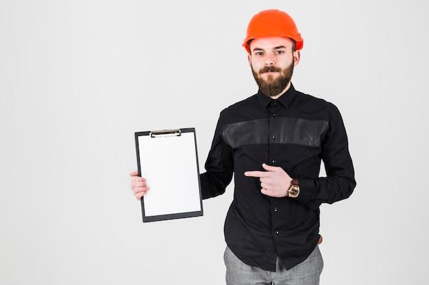 白い背景上でクリップボードを指している若いひげの建築家