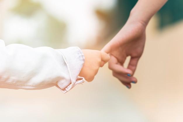 Крупный план брат, держащий палец сестры