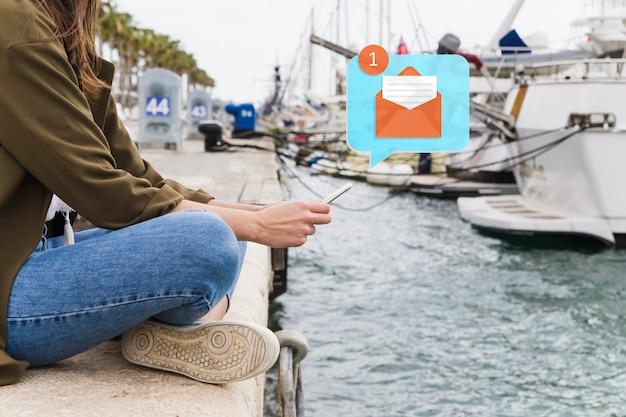 携帯電話で海岸のテキストメッセージに座っている女性の側面図