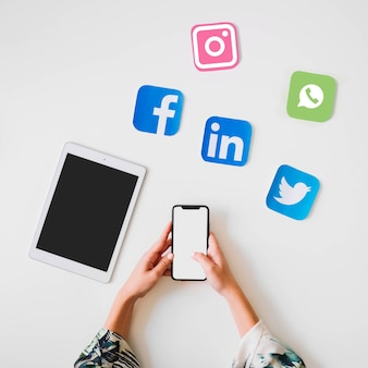 Человеческая рука, держащая мобильный телефон возле цифровой планшета и яркие значки социальных сетей