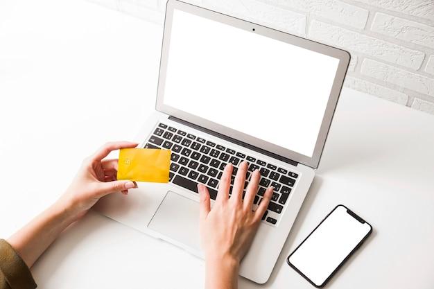 人間の手、クレジットカードを持って、携帯電話でラップトップに入力
