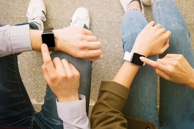 スマートな腕時計を一緒に着ているカップルの上昇した眺め