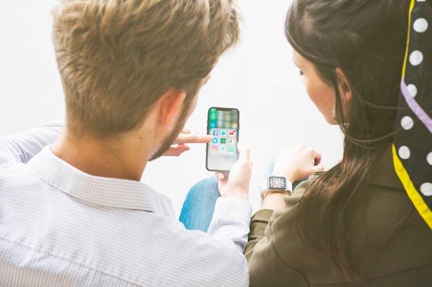 スマートな時計と接続して携帯電話でアプリケーションを使用している友人