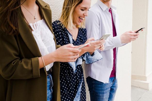 Группа счастливых друзей, стоящих вне, глядя на мобильный телефон