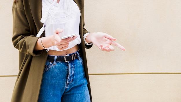 Средняя часть женщины, носящая длинный куртка, стоящая с мобильным телефоном