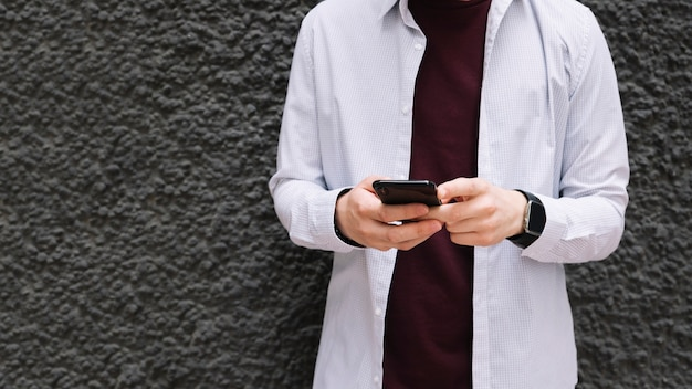 携帯電話と黒のテクスチャの壁の前に立っている男のクローズアップ