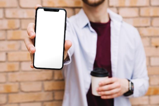 空の白い画面でスマートフォンを示す男の手のクローズアップ