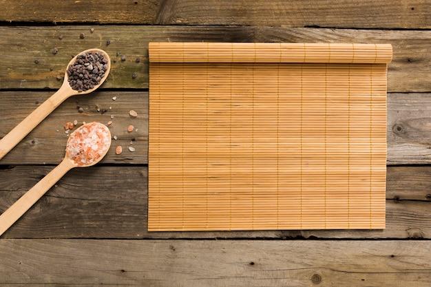 木製の背景にマット付きの木製スプーンでピンクと黒の塩
