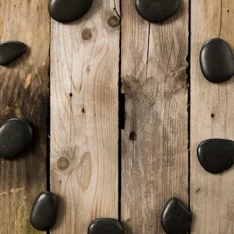 錆びたテーブルの上に円形を形成する黒い小石