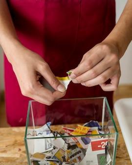 ガラスの容器の上に紙を引き裂く女性の手