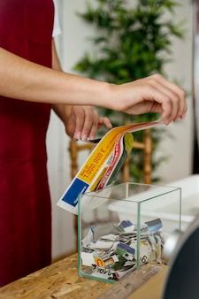 透明なガラス容器の上に紙を引き裂く女性の手のクローズアップ