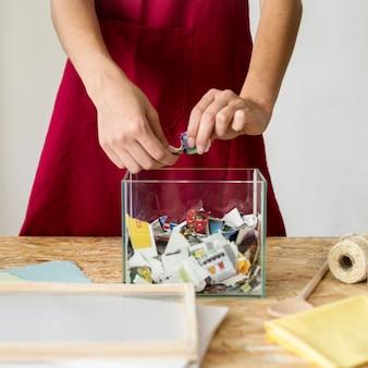 ワークショップでガラス容器の上に紙を引き裂く女性の手