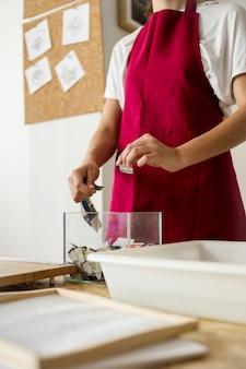 ガラスの容器に紙の断片を入れている女性の手