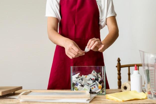ガラス容器の上に紙を引き裂く女性の手の中央部の図