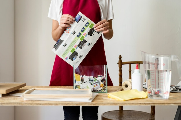 木製の机の後ろに紙を持っている女性の中央部の図