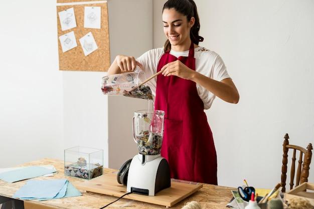 Улыбаясь молодая женщина, подготовка к измельчения бумаги в блендере