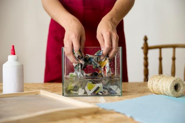 木製の机の上で水の中で紙を混合する女性の手