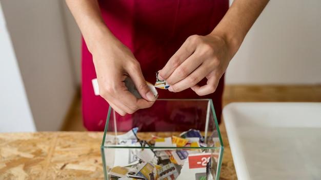 ガラスの容器の上に新聞を引き裂く女性の手