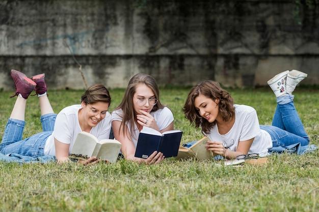 芝生の上に横たわる読書大学の学生の友達