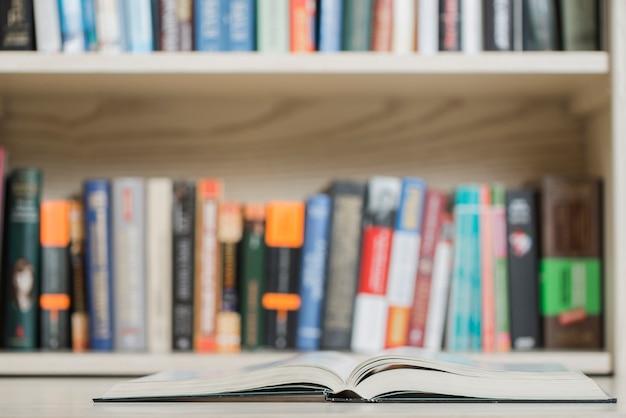 Открытая книга возле книжной полки