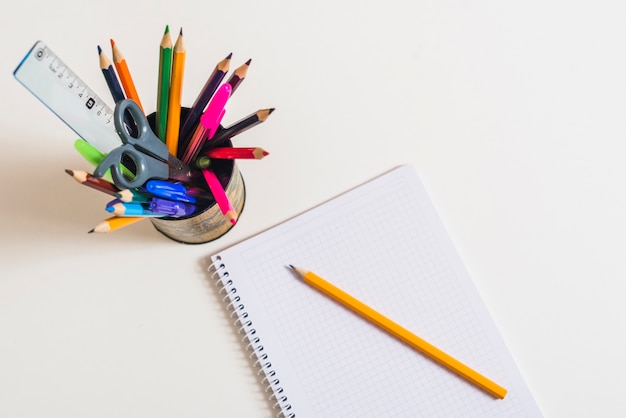 Ноутбук с карандашом возле письменных принадлежностей