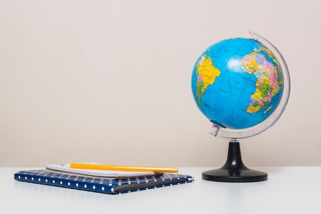 Глобус рядом с блокнотами и карандашом