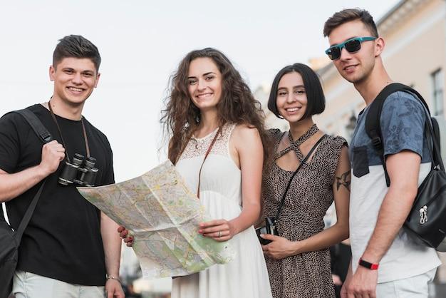 Друзья, стоящие с рюкзаками и картой